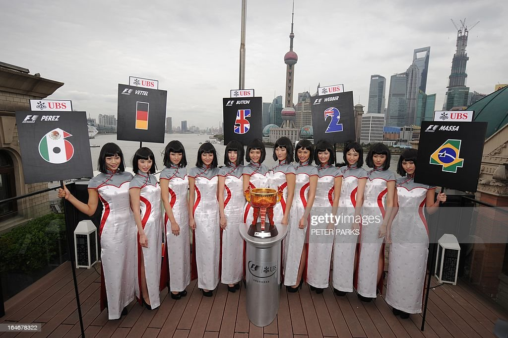 Grid girls for the upcoming Chinese Formula One Grand Prix pose behind the winner's trophy in their new outfits designed by local designer Simon Wang in Shanghai on March 26, 2013. The Chinese Formula One Grand Prix will be held in Shanghai on April 12-14. AFP PHOTO / Peter PARKS