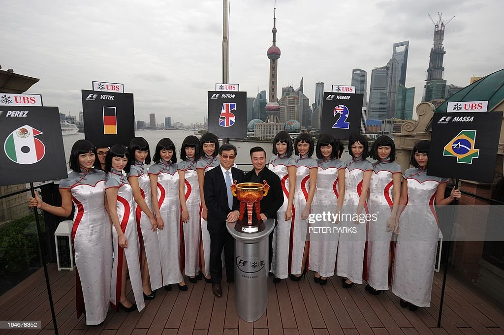 Grid girls for the upcoming Formula One Chinese Grand Prix show off new outfits designed by celebrated local designer Simon Wang (centre R) who stands with David Li (centre L), chairman and country head of UBS China and the trophy (C), with a view of Shanghai on March 26, 2013. The 10th Formula One Chinese Grand Prix will be held in Shanghai on April 14. AFP PHOTO/Peter PARKS