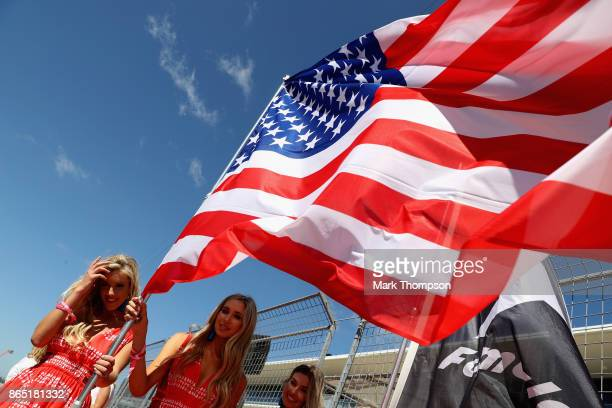 Grid girls hold a USA flag before the United States Formula One Grand Prix at Circuit of The Americas on October 22 2017 in Austin Texas