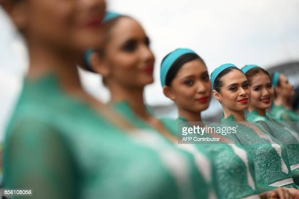 Grid girls pose for photographs before the start of the Formula One Malaysia Grand Prix in Sepang on October 1 2017 / AFP PHOTO / MANAN VATSYAYANA