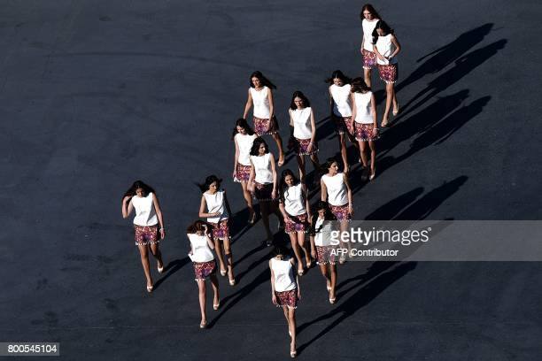 Grid girls walk at the Baku City Circuit during the qualifying session for the Formula One Azerbaijan Grand Prix in Baku on June 24 2017 / AFP PHOTO...
