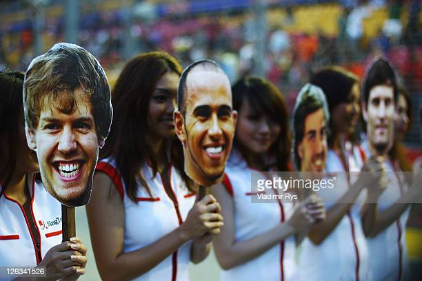 Grid girls wear masks featuring Sebastian Vettel Lewis Hamilton Fernando Alonso and Mark Webber before the Singapore Formula One Grand Prix at the...