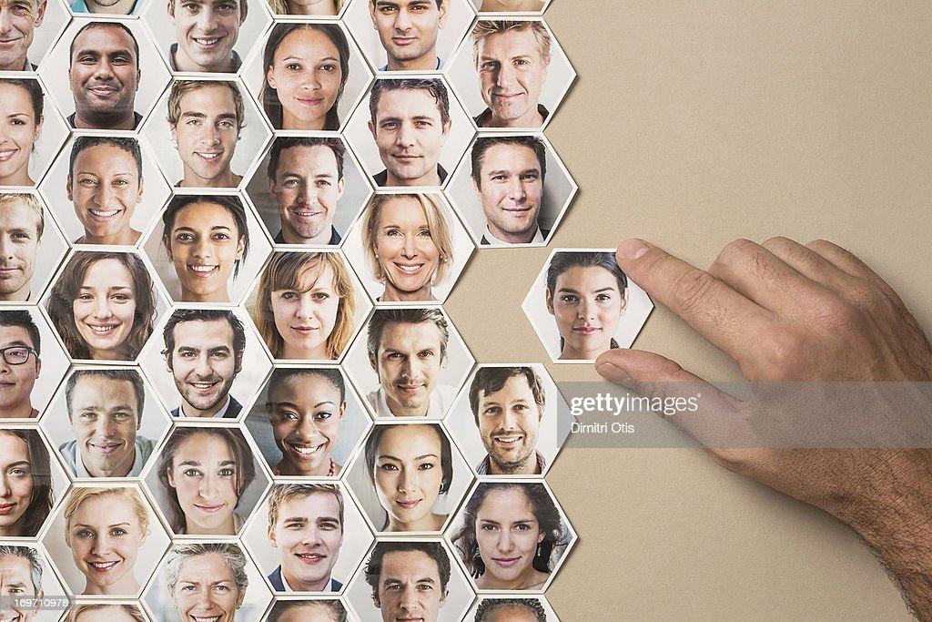 Grid of hexagonal portraits, hand adding new one : Stock Photo