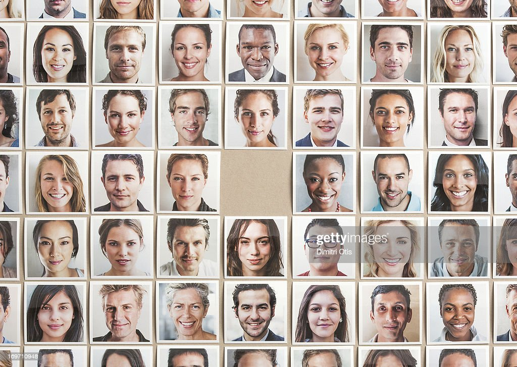 Grid of portrait prints, one missing in centre : Stock Photo