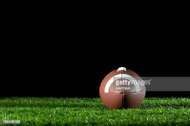 Gridiron ball on the grass at night.