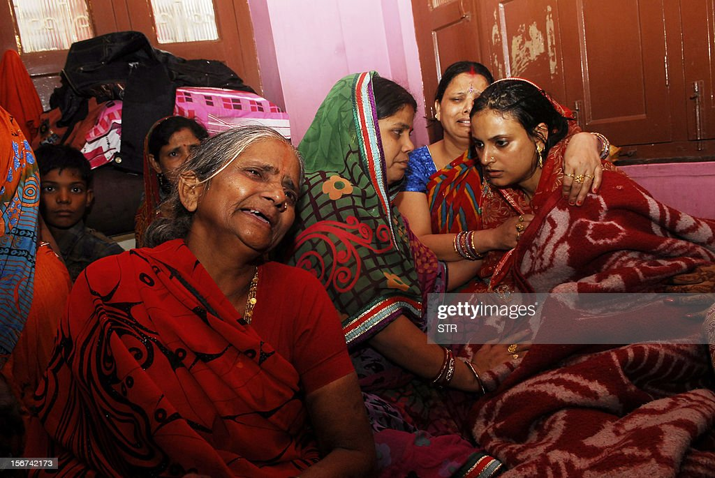 Grief-stricken family members mourn the death of eighteen month old child Rithvik who died in a stampede which killed 18 women and children when a makeshift bridge collapsed at a Hindu festival, in Patna on November 20, 2012. India on Tuesday launched an inquiry into a stampede which killed 18 women and children when a makeshift bridge collapsed at a Hindu festival, as devotees returned to pray at the scene of the tragedy.