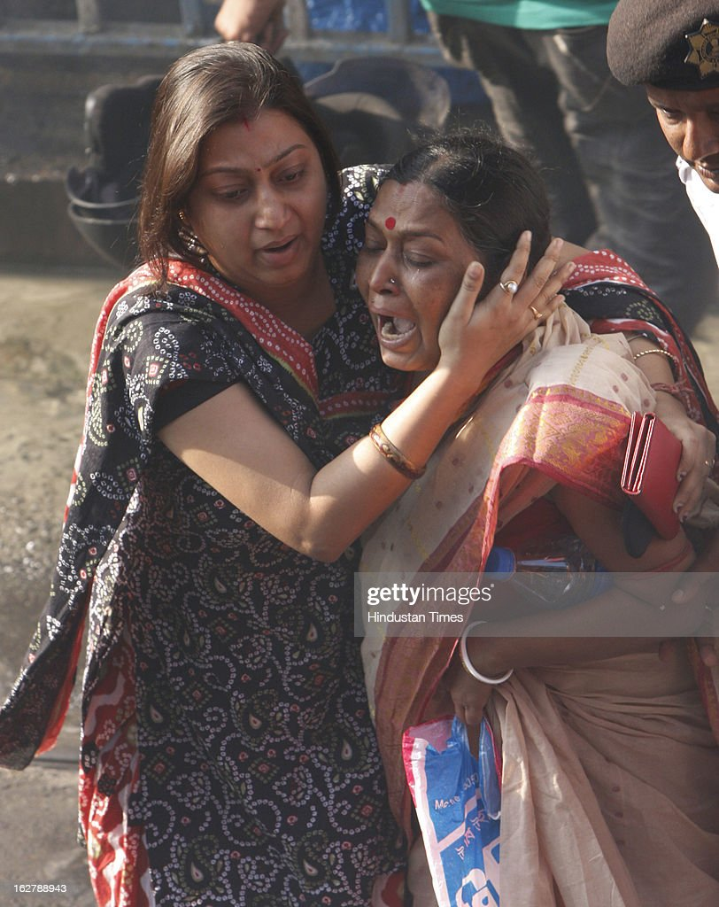Grieved family members of shop owner whose shop was charred after fire engulfed a multi-storey market complex at Sealdah on February 27, 2013 in Kolkata, India. At least 19 people were killed in it. A dozen people were also critically injured in the fire that broke out at about 3 am at Sealdah in Central Kolkata, when many victims (Labours & shop keepers) were asleep. Even as 26 fire tenders battled the leaping flames and firemen scrambled to rescue people, many were feared trapped inside the market that houses plastic items, thermocol and paper godowns.