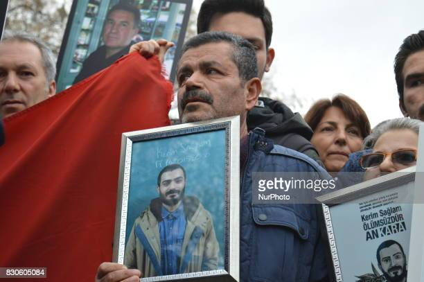 A grieved father mourns as he holds his son's portrait during a commemoration to the 1st anniversary of the Guven Park bombing in Ankara Turkey on...
