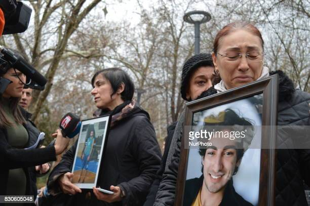 A grieved mother mourns as she holds her son's portrait during a commemoration to the 1st anniversary of the Guven Park bombing in Ankara Turkey on...