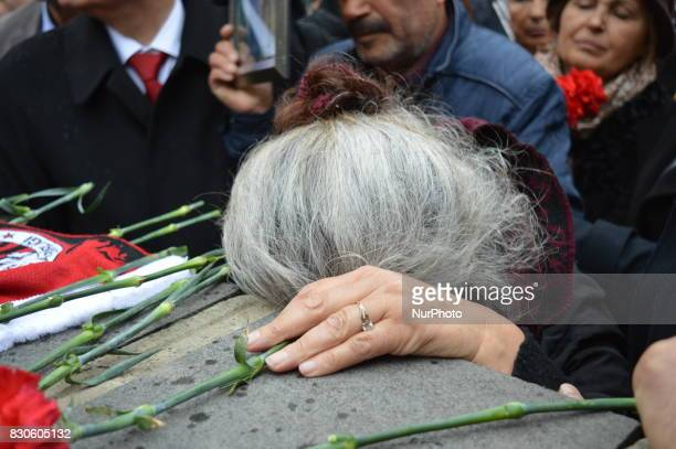 A grieved mother mourns as she places a flower for her son during a commemoration to the 1st anniversary of the Guven Park bombing in Ankara Turkey...