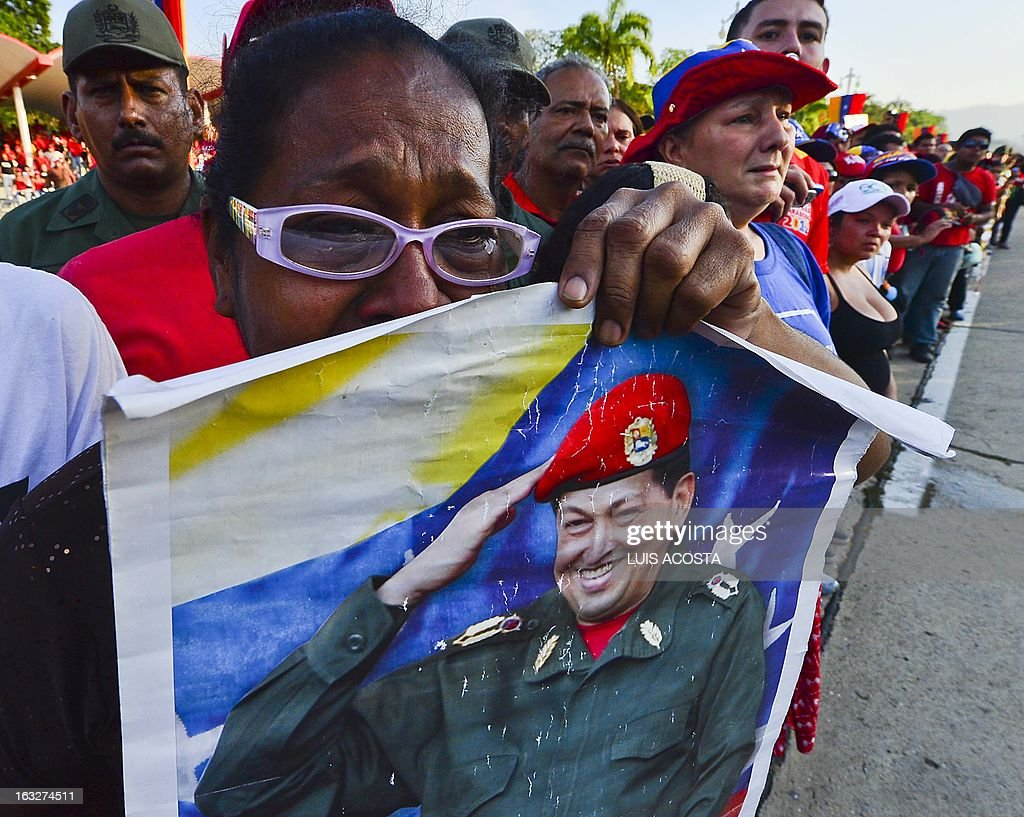 A grieving crowd accompanies the coffin of Venezuelan President Hugo Chavez upon its arrival at the Military Academy, on March 6, 2013, in Caracas. The flag-draped coffin of Venezuelan leader Hugo Chavez was borne through throngs of weeping supporters on Wednesday as a nation bade farewell to the firebrand leftist who led them for 14 years. AFP PHOTO/Luis Acosta