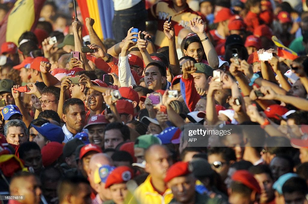 A grieving crowd accompanies the coffin of Venezuelan President Hugo Chavez upon its arrival at the Military Academy, on March 6, 2013, in Caracas. The flag-draped coffin of Venezuelan leader Hugo Chavez was borne through throngs of weeping supporters on Wednesday as a nation bade farewell to the firebrand leftist who led them for 14 years.