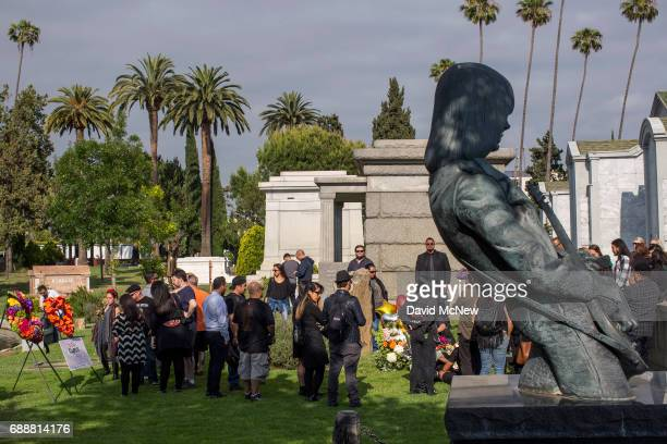 Grieving fans gather at the grave of Chris Cornell near a memorial statue on the grave of Johnny Ramone of the band The Ramones after funeral...