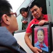 A grieving parent holds a portrait of his deceased daughter from a window of a bus which came to a standstill during a protest along a highway on the...