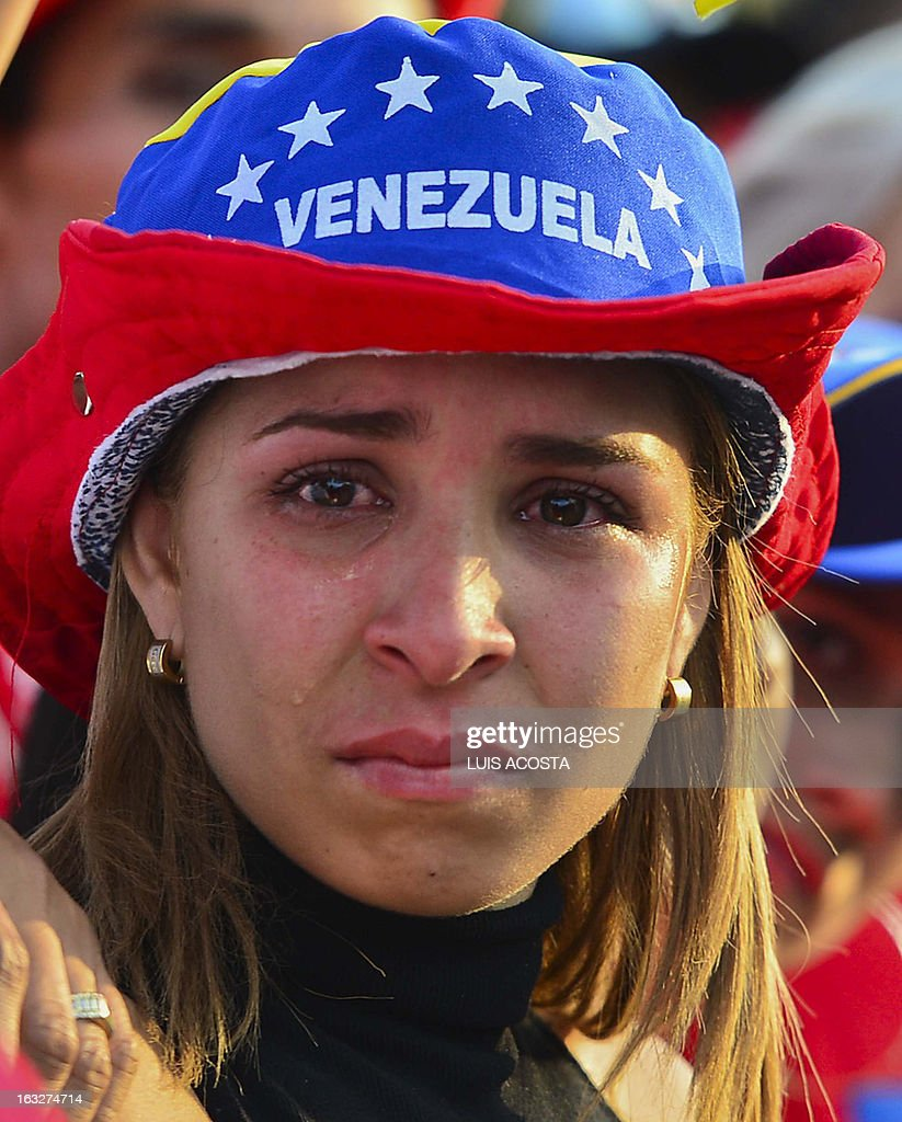 A grieving supporter cries as the coffin of Venezuelan President Hugo Chavez arrives at the Military Academy, on March 6, 2013, in Caracas. The flag-draped coffin of Venezuelan leader Hugo Chavez was borne through throngs of weeping supporters on Wednesday as a nation bade farewell to the firebrand leftist who led them for 14 years. AFP PHOTO/Luis Acosta