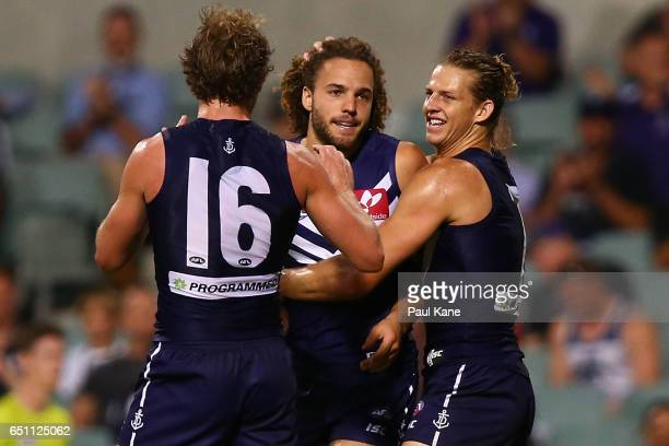 Griffin Logue of the Dockers is congratulated by David Mundy and Nathan Fyfe after kicking his first goal during the JLT Community Series AFL match...