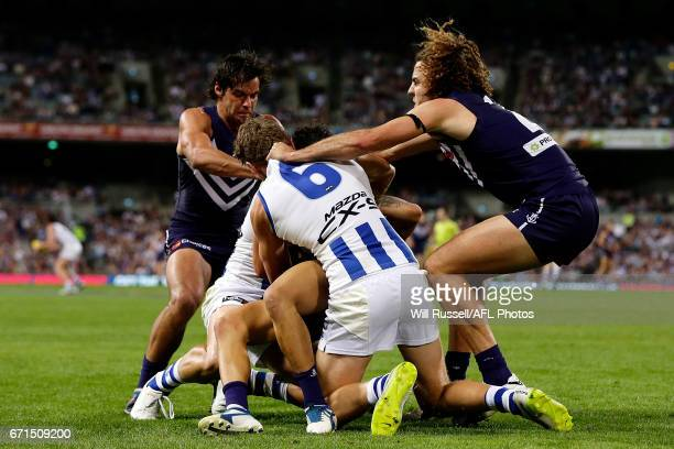 Griffin Logue of the Dockers tries to pull Lachlan Hansen of the Kangaroos off Michael Walters of the Dockers during the round five AFL match between...