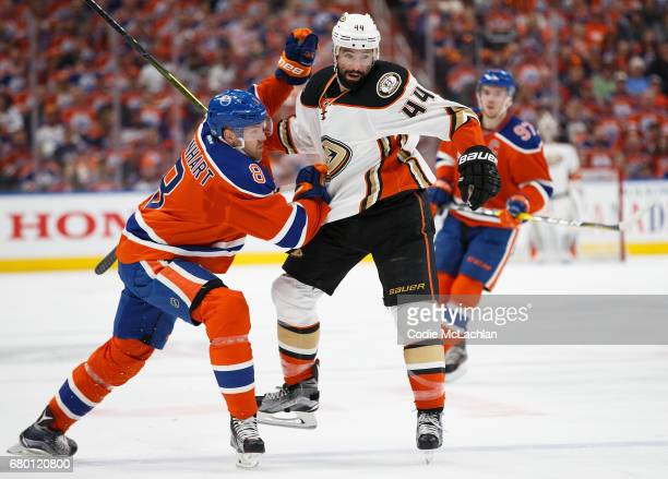 Griffin Reinhart of the Edmonton Oilers hits Nate Thompson of the Anaheim Ducks in Game Six of the Western Conference Second Round during the 2017...