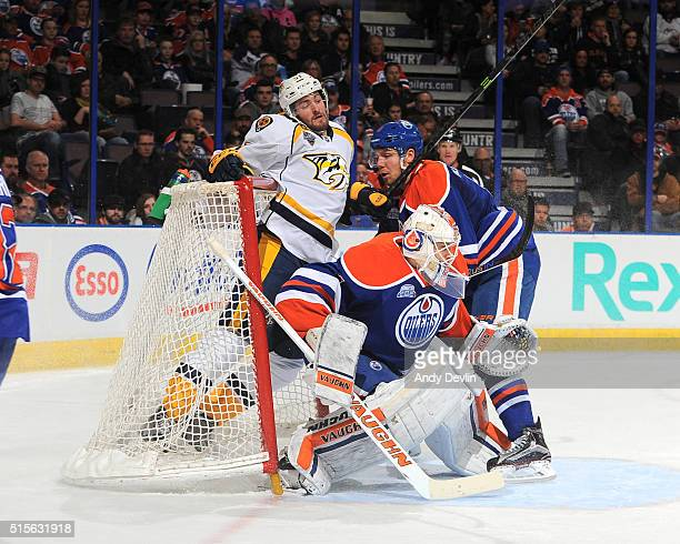 Griffin Reinhart of the Edmonton Oilers pushes Austin Watson of the Nashville Predators into the net on March 14 2016 at Rexall Place in Edmonton...