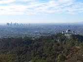 A photo of Griffith Observatory and Downtown Los Angeles as taken from on top of the mountain.