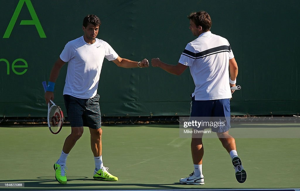 Grigor Dimitrov of Bulgaria and Frederik Nielsen of Denmark high five during a doubles match against Tommy Haas of Germany and Xavier Malisse of...