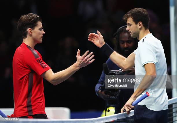 Grigor Dimitrov of Bulgaria celebrates victory in his Singles match as he shakes hands with Dominic Thiem of Austria during day two of the Nitto ATP...