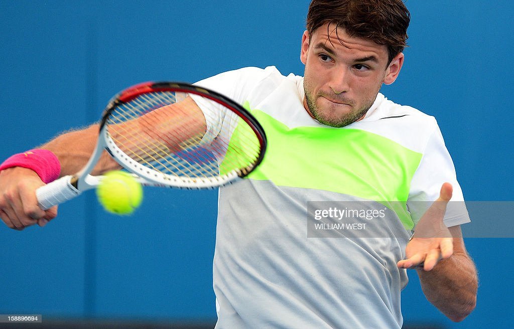 Grigor Dimitrov of Bulgaria hits a backhand return against Milos Raonic of Canada in the second at the Brisbane International tennis tournament on...
