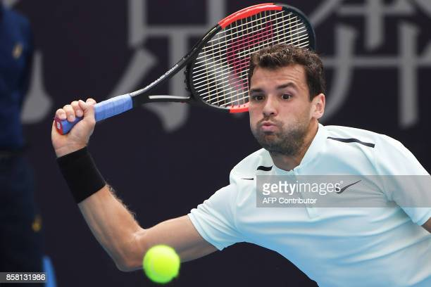 Grigor Dimitrov of Bulgaria hits a return during his men's singles quarterfinal against Roberto Bautista Agut of Spain at the China Open tennis...