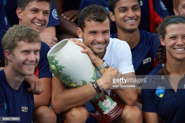 Grigor Dimitrov of Bulgaria holds the Rookwood Cup with some of the ball boys and girls after winning the match against Nick Kyrgios of Australia...