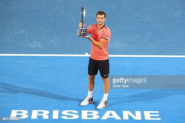 Grigor Dimitrov of Bulgaria holds the Roy Emerson trophy after winning the Men's Final against Kei Nishikori of Japan during day eight of the...
