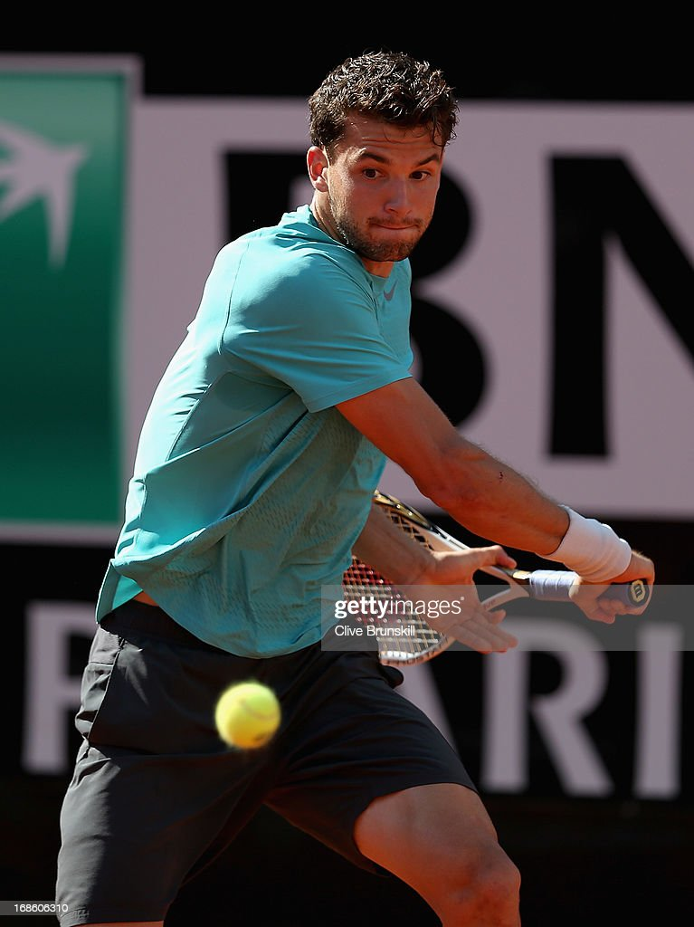 <a gi-track='captionPersonalityLinkClicked' href=/galleries/search?phrase=Grigor+Dimitrov&family=editorial&specificpeople=4332557 ng-click='$event.stopPropagation()'>Grigor Dimitrov</a> of Bulgaria plays a backhand against Marcos Baghdatis of Cyprus in their first round match during day one of the Internazionali BNL d'Italia 2013 at the Foro Italico Tennis Centre on May 12, 2013 in Rome, Italy.