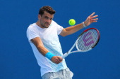 Grigor Dimitrov of Bulgaria plays a backhand in his first round match against Julien Benneteau of France during day one of the 2013 Australian Open...
