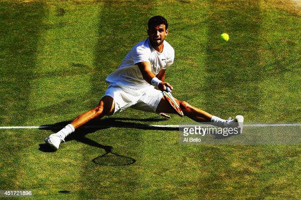Grigor Dimitrov of Bulgaria plays a shot whilst sitting down after slipping over during the Gentlemen's Singles semifinal match against Novak...