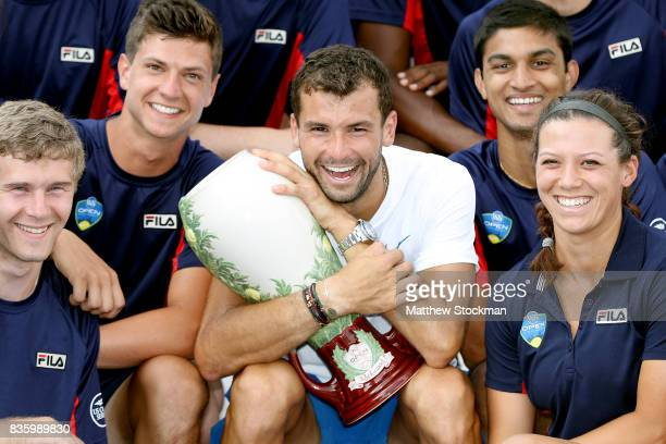Grigor Dimitrov of Bulgaria poses for photographers with the ball persons after his win over Nick Kyrgios of Australia during the men's final on day...