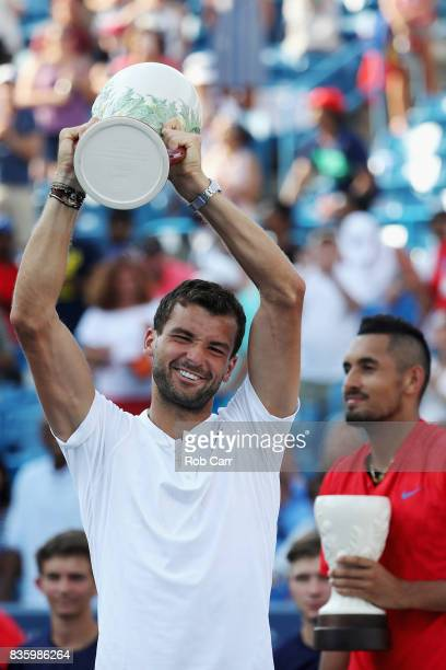 Grigor Dimitrov of Bulgaria poses with the trophy after defeating Nick Kyrgios of Australia to win the men's final during Day 9 of of the Western and...