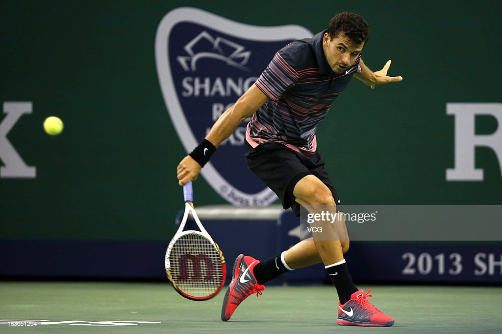 Grigor Dimitrov of Bulgaria returns a ball to Kei Nishikori of Japan on day two of the Shanghai Rolex Masters at the Qi Zhong Tennis Center on October 8, 2013 in Shanghai, China.
