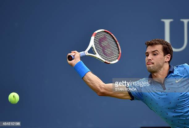 Grigor Dimitrov of Bulgaria returns a shot to Gael Monfils of France during their 2014 US Open men's singles match at the USTA Billie Jean King...