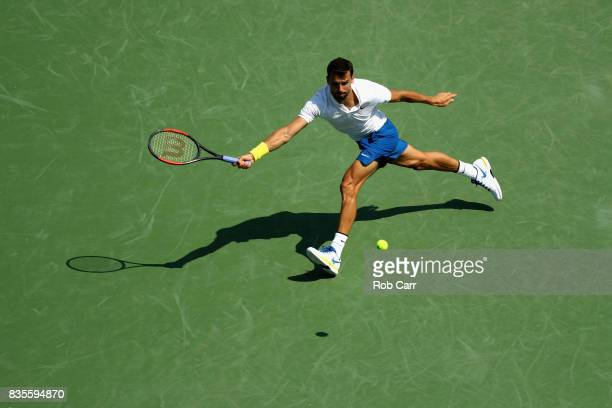 Grigor Dimitrov of Bulgaria returns a shot to John Isner during Day 8 of the Western and Southern Open at the Linder Family Tennis Center on August...