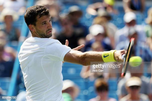 Grigor Dimitrov of Bulgaria returns a shot to John Isner to advance to the finals during Day 8 of the Western and Southern Open at the Linder Family...