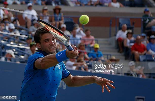 Grigor Dimitrov of Bulgaria returns the ball to Gael Monfils of France during men's singles fourth round match on Day Nine of the 2014 US Open at the...