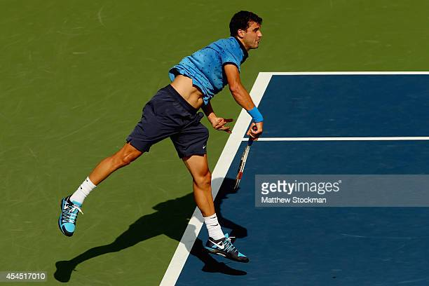 Grigor Dimitrov of Bulgaria serves against Gael Monfils of France during their men's singles fourth round match on Day Nine of the 2014 US Open at...
