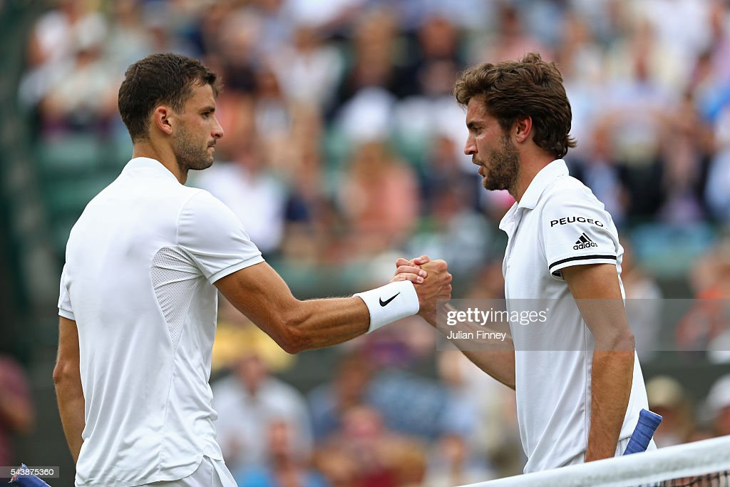 Grigor Dimitrov of Bulgaria shakes hands with Gilles Simon of France following victory during the Men's Singles second round match on day four of the Wimbledon Lawn Tennis Championships at the All England Lawn Tennis and Croquet Club on June 30, 2016 in London, England.