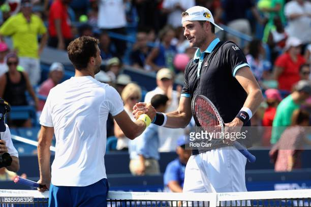 Grigor Dimitrov of Bulgaria shakes hands with John Isner after defeating him to advance to the finals during Day 8 of the Western and Southern Open...