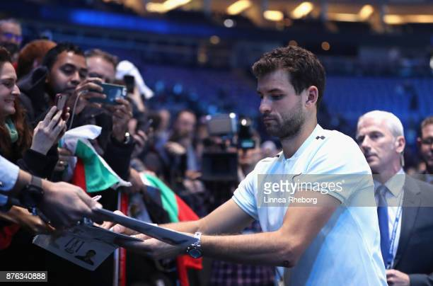 Grigor Dimitrov of Bulgaria signs autographs as he celebrates victoy following the singles final against David Goffin of Belgium during day eight of...