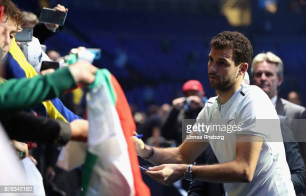 Grigor Dimitrov of Bulgaria signs autographs following victory in the mens singles final against David Goffin of Belgium during day eight of the 2017...