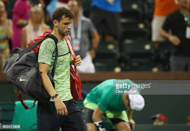 Grigor Dimitrov of Bulgaria walks off court after his three set defeat by Jack Sock of the United States in their third round match during day nine...