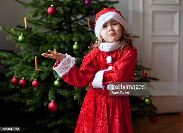 gril in santa claus costume making fun at home