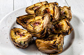 Grilled artichokes with salt and pepper on a plate.