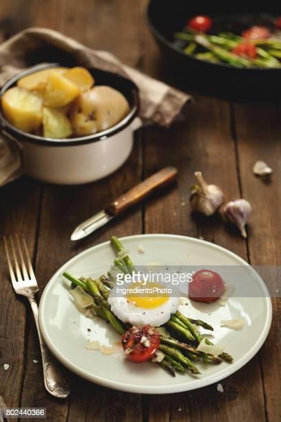 Asperges grillées bébé avec des œufs et l'ail sur la table en bois.