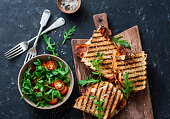 Grilled bacon, mozzarella sandwiches on wooden cutting boards and arugula, cherry tomato salad on dark background, top view.Delicious breakfast or snack, flat lay